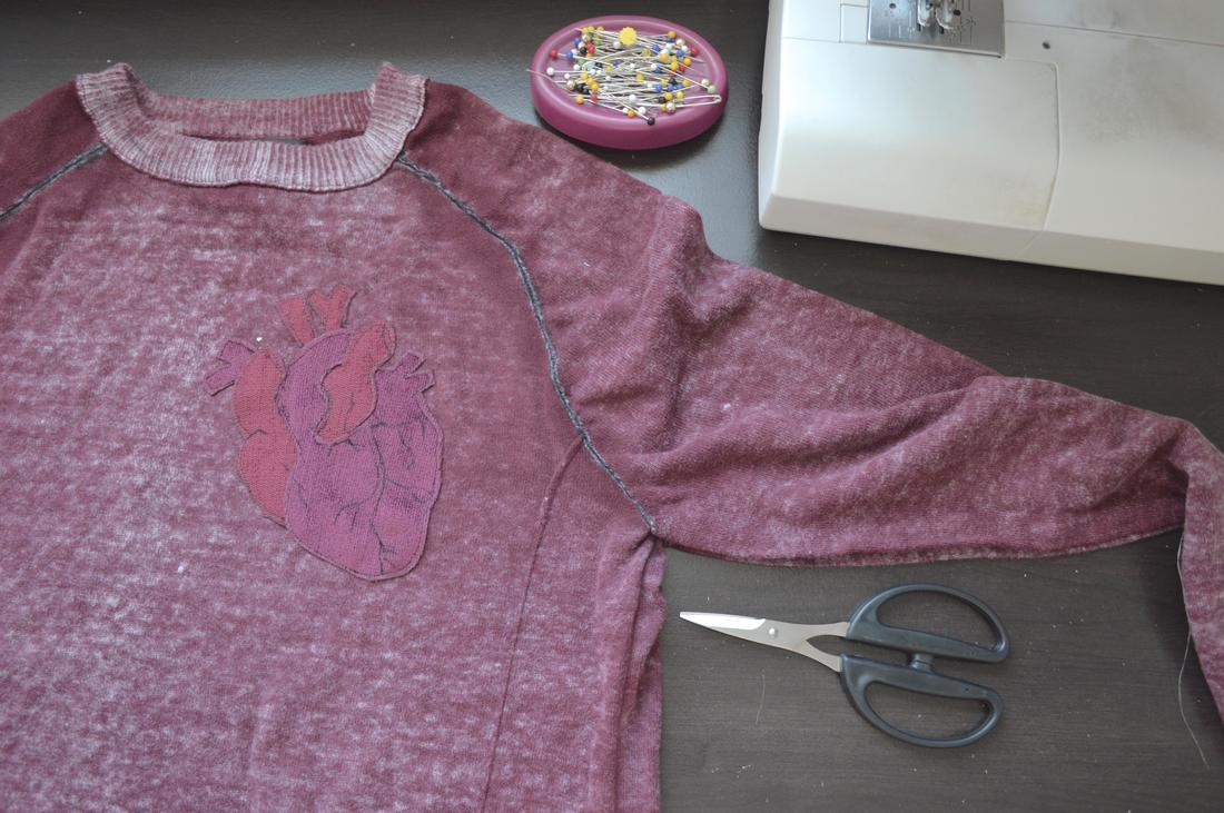 topstitching the anatomical heart onto the sweater