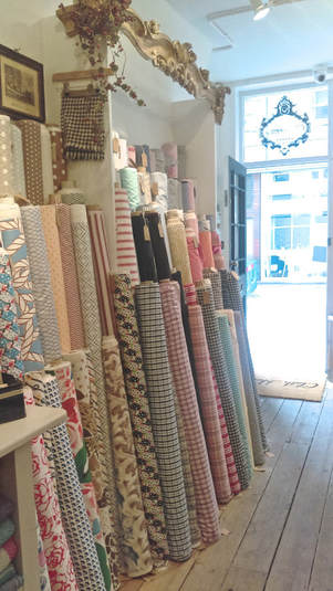 Rolls of fabric displayed in a shabby chic cloth house london store